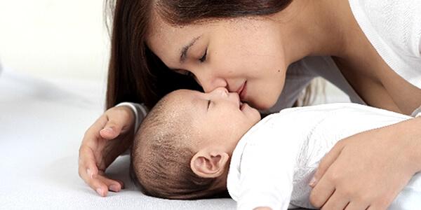 赤ちゃんとスキンシップするお母さん