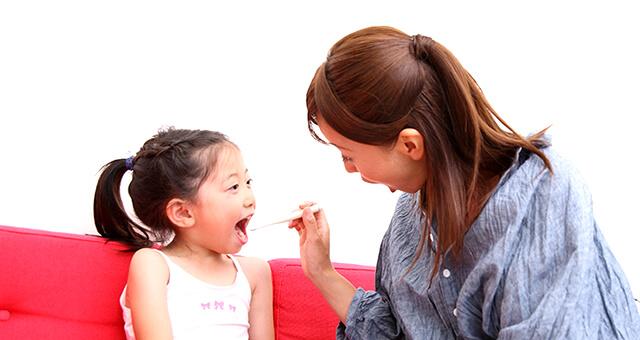 子供の歯を仕上げ磨きするお母さん