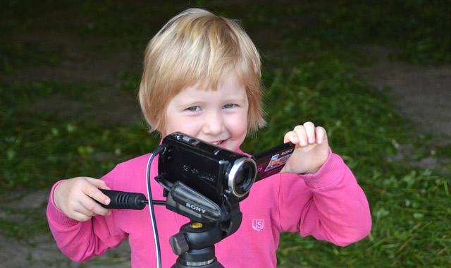 三脚のビデオカメラを操作する子供